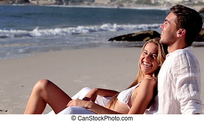 Attractive couple relaxing on the beach and talking together