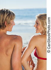 Attractive couple relaxing on the beach together