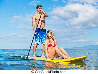 Couple Sharing Stand Up Paddle Board - Attractive Couple...