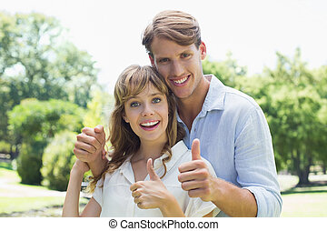 Attractive couple smiling at camera and showing thumbs up in the park on a sunny day