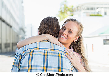 Attractive couple standing and hugging on a sunny day in the...
