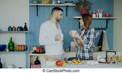 Attractive couple talking and drinking coffee in the kitchen in the morning at home