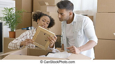 Attractive couple unpacking their things in new home -...