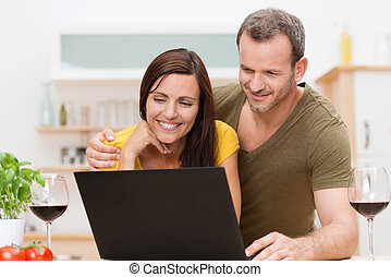 Attractive couple using a laptop in the kitchen