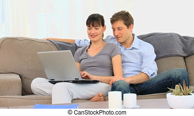 Attractive couple using a laptop