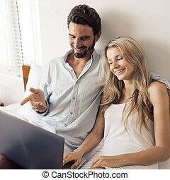 Attractive couple using laptop in bedroom.