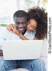 Attractive couple using laptop toge