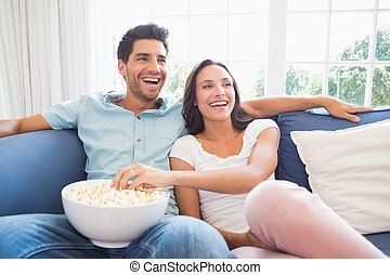 Attractive couple watching tv on the couch