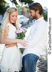 Attractive couple with bunch of flowers