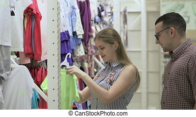Attractive couple - young woman with her husband - chooses clothes in store. Beautiful woman considering t-shirts in the supermarket. Pretty woman buys clothes in mall. Stock video footage.