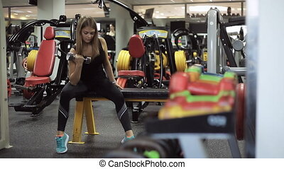 attractive, cute girl with blond hair is engaged in the gym, lifting weights and developing the biceps muscle in his arms. Exercise is carried out smoothly and safely.