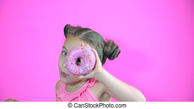 Attractive cute little girl holding donuts with icing to her hands smiling looks at the camera and brings them to her face looking to look at collection of sweet donuts with pink icing. Portrait child