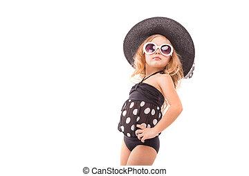Attractive cute little girl in in black swimwear, white sunglasses and black hat