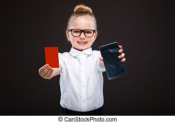 Attractive cute young girl in white shirt and black trousers hold red card and shows the phone