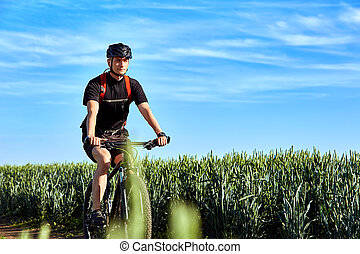 Attractive cyclist rides on the road in a field on a bright sunny day against blue sky.