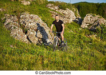 Attractive cyclist riding the bike on summer trail near beautiful big rocks.