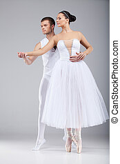 attractive dancing couple holding hands. beautiful ballet dancers tiptoe and looking