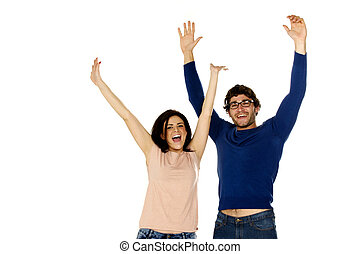 Attractive dark haired couple stood cheering and celebrating isolated on a white background