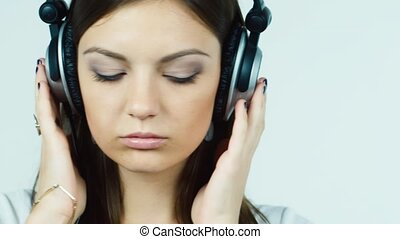 Attractive dark-haired woman listening to music on headphones and smiling