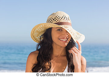 Attractive dark haired woman with straw hat posing on the beach