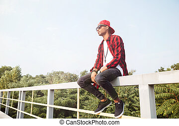 Attractive dark skinned young boy sitting against nature background
