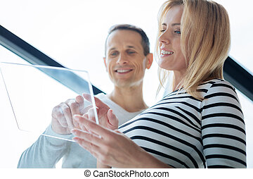 Attractive delighted woman holding a tablet