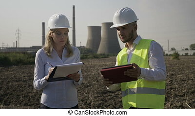 Attractive developer business woman with helmet noting in her notebook working progress report of young engineer using tablet pc near refinery platform