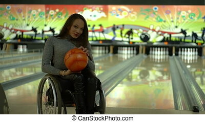 Attractive disabled girl in a wheelchair having fun in the bowling, dancing with a bowling ball