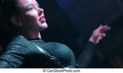 Attractive Dj girl in black top energy dance at turntable in nightclub.