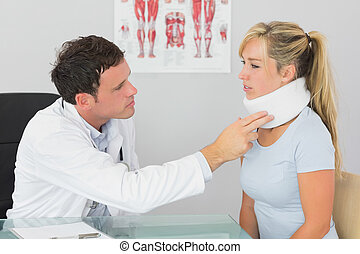 Attractive doctor examining neck of a patient