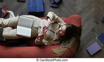Attractive dreamy girl in glasses on the red sofa reading love letter and cheerfully smiling surrounded by many books on the floor