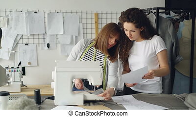 Attractive dressmakers are looking at sketches and working with sewing machine, then checking stitches and adjusting equipment. Professional teamwork concept.