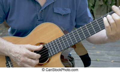 Attractive elderly senior man learning to play acoustic guitar outside