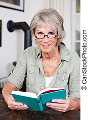 Attractive elderly woman reading a book