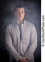 Attractive elegant young man standing with smoke around him