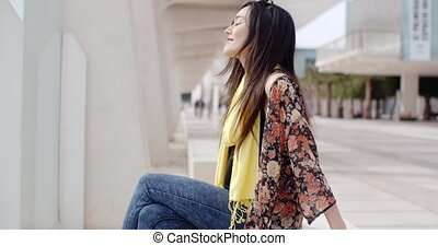 Attractive elegant young woman relaxing in town