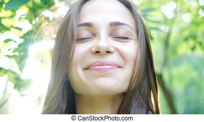 Attractive face near a cute girl, on which the wind is slightly blowing in a warm summer park against the background of bright sunlight. Cute young girl with green eyes looks and smiles at the camera.