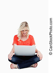 Attractive fair-haired woman sitting cross-legged while looking at her laptop