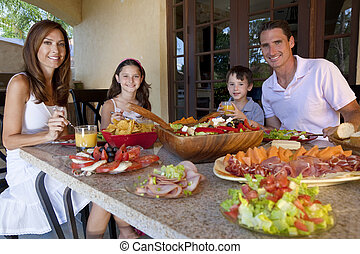 An attractive happy, smiling family of mother, father, son and daughter eating healthy food with ham, cheese and fresh salad at an outdoor table at home.