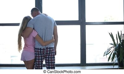 Attractive family in love embrace by the window