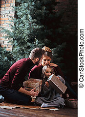 Attractive family opens presents while sitting on a floor next to the Christmas tree.