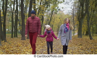 Attractive family walking along autumn path