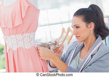Attractive fashion designer cutting dress