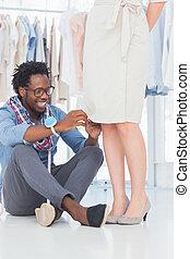 Attractive fashion designer fixing needles on dress