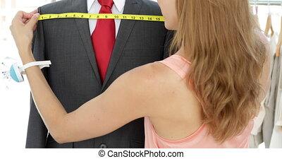 Attractive fashion designer measuring suit on mannequin in her studio