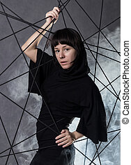 attractive fashionable woman wearing a gothic black dress, poses in white smoke on a grey background.