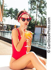 Attractive fashionable young woman holding a straw