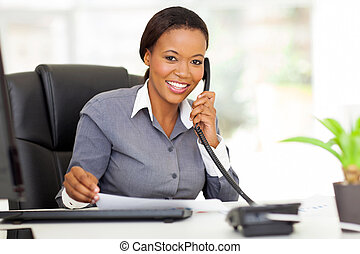 female african office worker talking on phone - attractive...