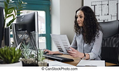 Attractive female architect working on the computer with color palatte in the modern office.