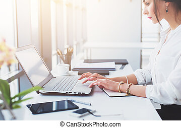 Attractive female assistant working, typing, using portable computer, concentrated, looking at the monitor. Office worker reading business e-mail.